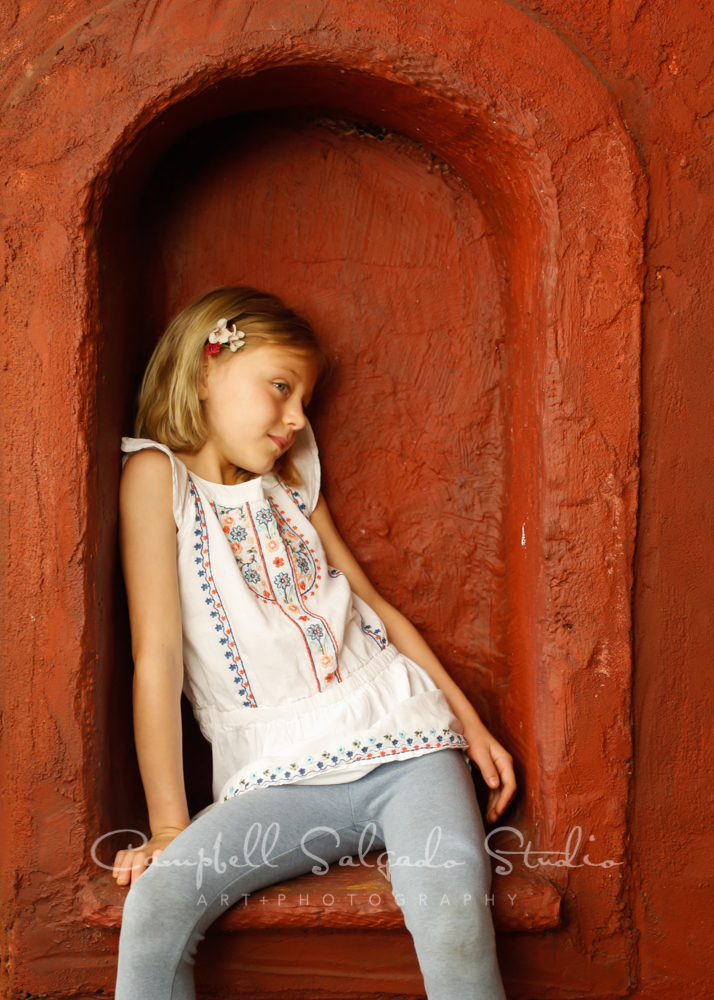Portrait of boy on red stucco background by child photographers at Campbell Salgado Studio in Portland, Oregon.