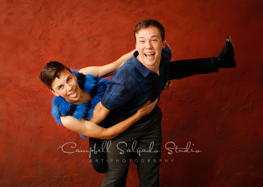 Portrait of brothers on red stucco background by family photographers at Campbell Salgado Studio in Portland, Oregon.