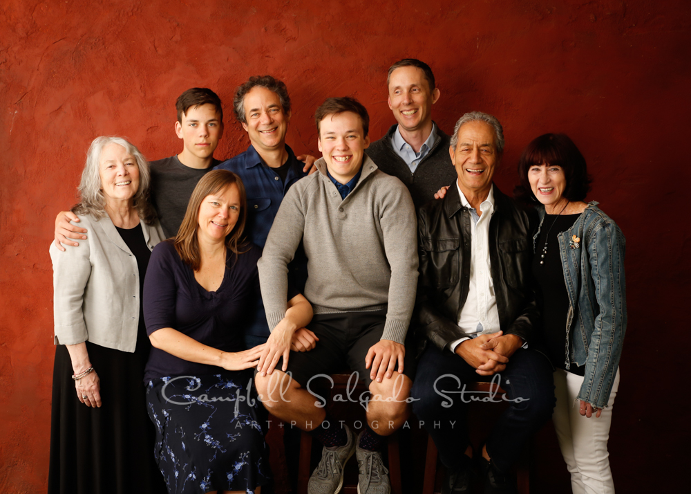 Portrait of multi generational family on red stucco background by family photographers at Campbell Salgado Studio in Portland, Oregon.