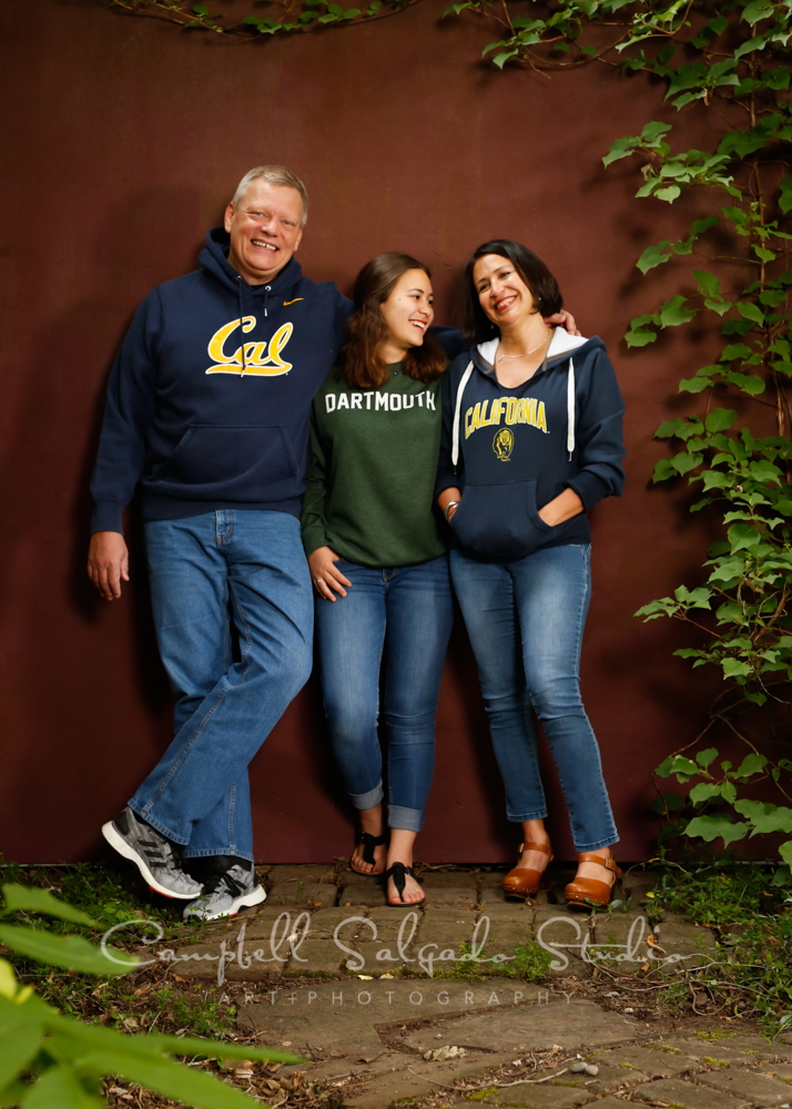 Portrait of family on plum stucco background by family photographers at Campbell Salgado Studio in Portland, Oregon.
