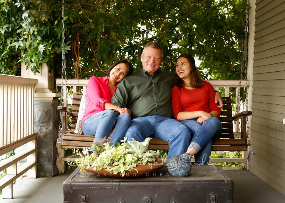 Portrait of family on porch swing background by family photographers at Campbell Salgado Studio in Portland, Oregon.