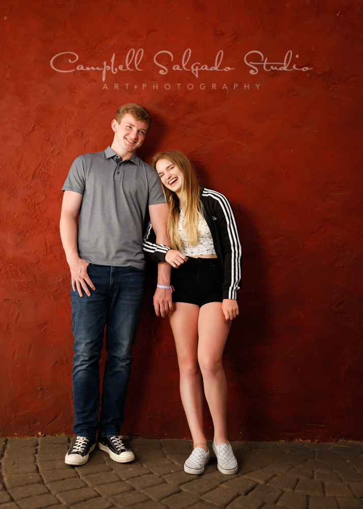 Portrait of teens on red stucco background by family photographers at Campbell Salgado Studio in Portland, Oregon.