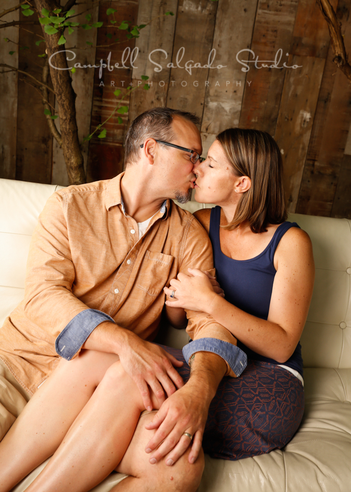Portrait of couple on wooden wall background by couples photographers at Campbell Salgado Studio in Portland, Oregon.