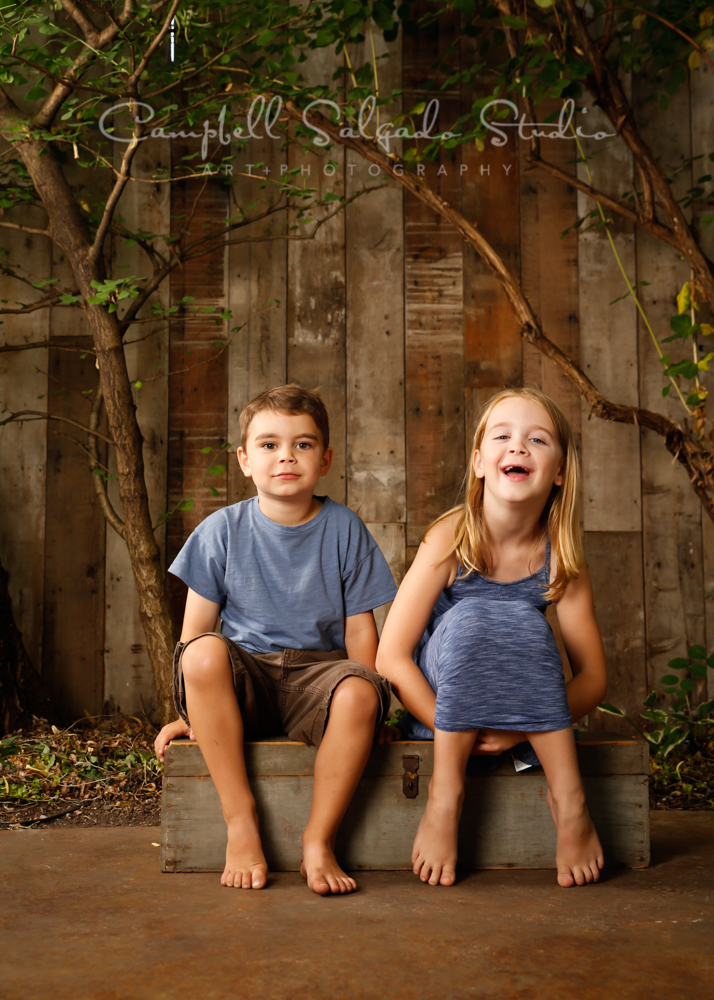 Portrait of children on wooden wall background by children's photographers at Campbell Salgado Studio in Portland, Oregon.