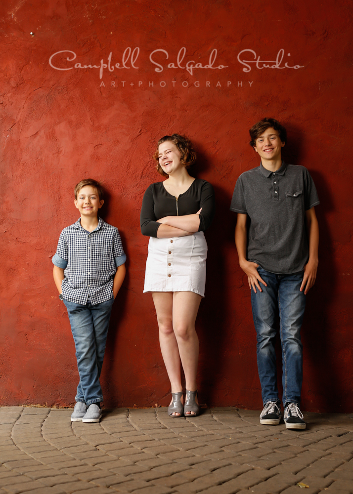 Portrait of children on red stucco background by family photographers at Campbell Salgado Studio in Portland, Oregon.