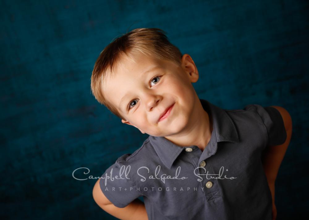Portrait of boy on deep ocean background by children's photographers at Campbell Salgado Studio in Portland, Oregon.