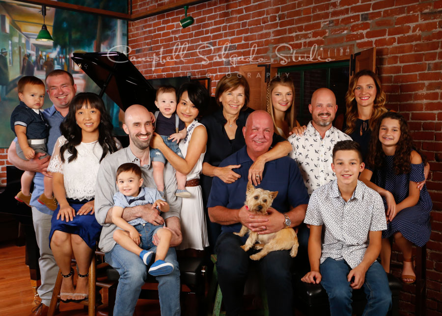 Portraits of multi generational family at piano store background by family photographers at Campbell Salgado Studio in Portland, Oregon.
