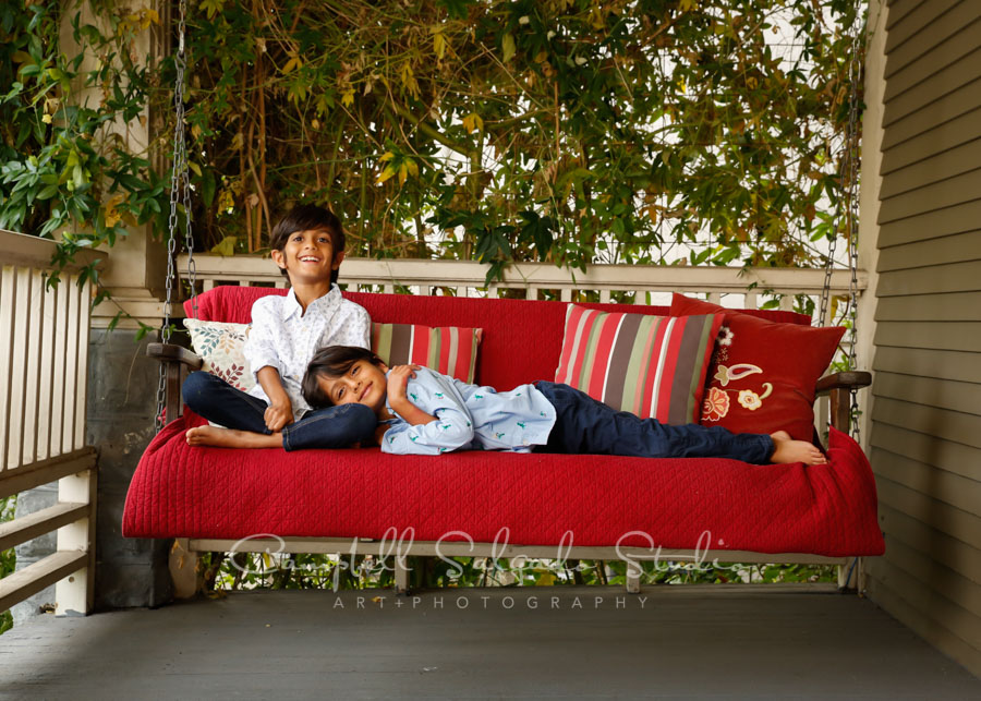Portrait of boys on porch swing background by childrens photographers at Campbell Salgado Studio in Portland, Oregon.