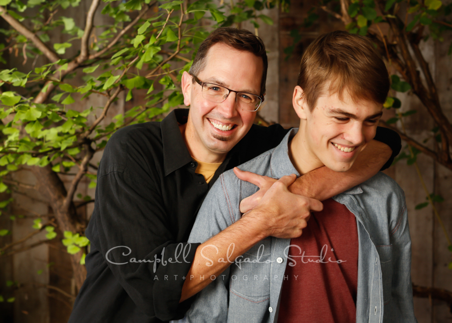Portrait of father and son on garden grove background by family photographers at Campbell Salgado Studio in Portland, Oregon.