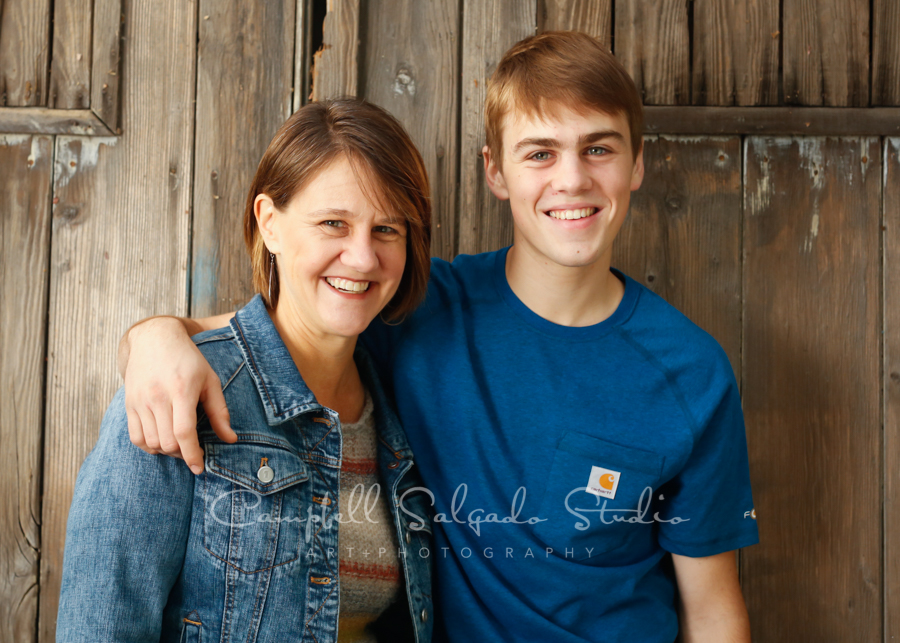 Portrait of mother and son on barn doors background by family photographers at Campbell Salgado Studio in Portland, Oregon.