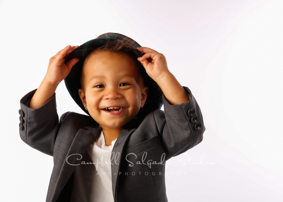 Portrait of boy on white background by child photographers at Campbell Salgado Studio in Portland, Oregon.