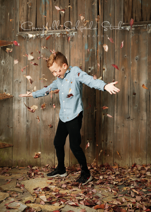 Portrait of child on barn doors background by child photographers at Campbell Salgado Studio in Portland, Oregon.