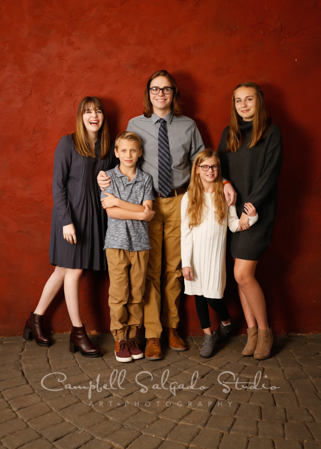 Portrait of cousins on red stucco background by family photographers at Campbell Salgado Studio in Portland, Oregon.
