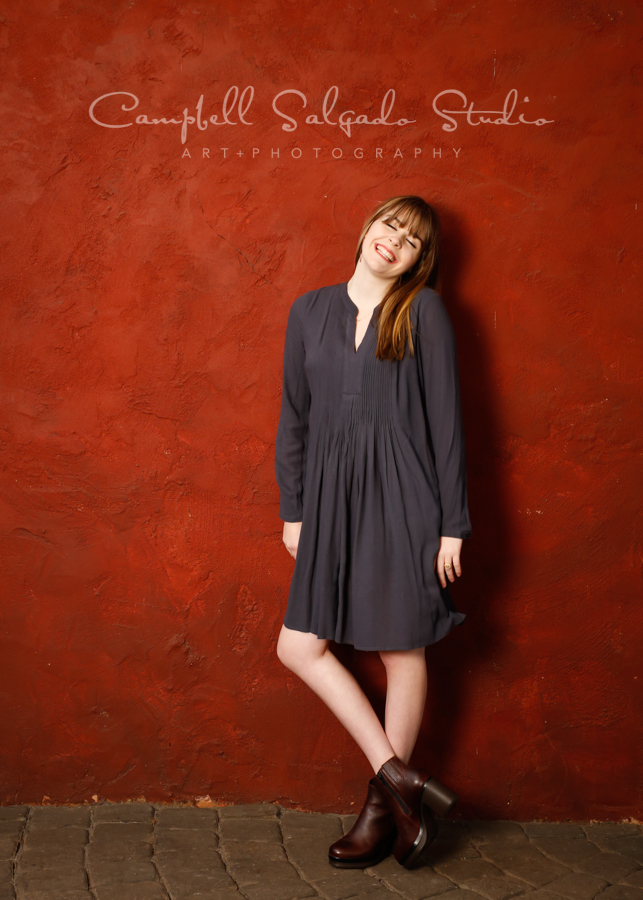 Portrait of girl on red stucco background by family photographers at Campbell Salgado Studio in Portland, Oregon.