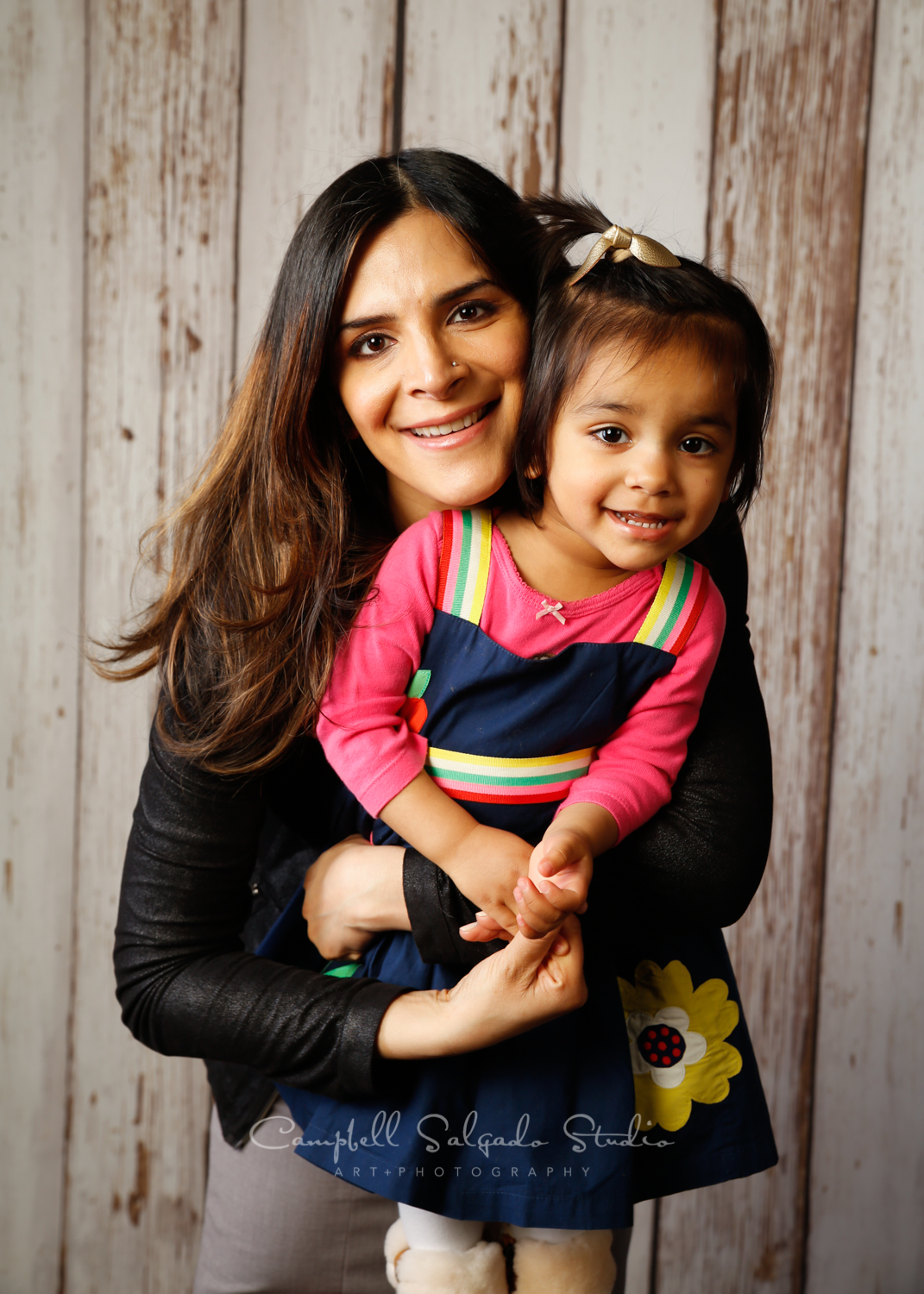 Portrait of mother and daughter on white fenceboards background by family photographers at Campbell Salgado Studio in Portland, Oregon.