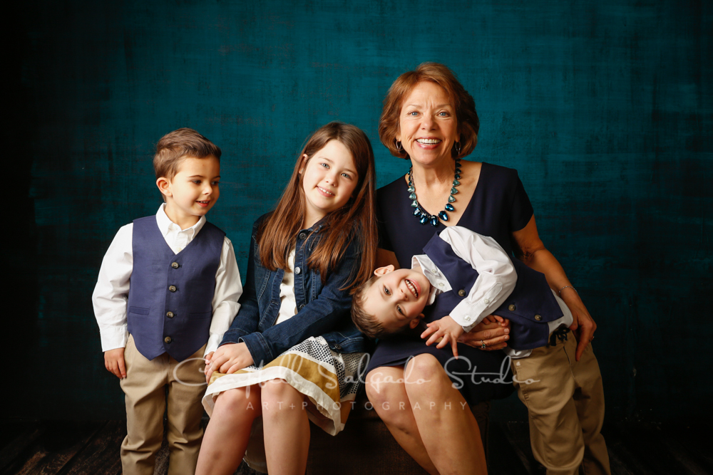 Portrait of multi-generational family on deep ocean background by family photographers at Campbell Salgado Studio in Portland, Oregon.