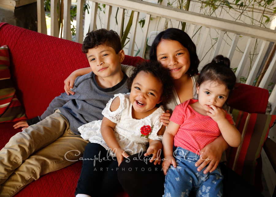 Portrait of children on porch swing background by child photographers at Campbell Salgado Studio in Portland, Oregon.