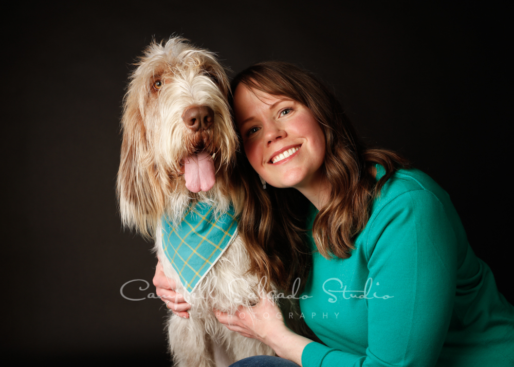 Portrait of woman and dog on black background by pet photographers at Campbell Salgado Studio in Portland, Oregon.