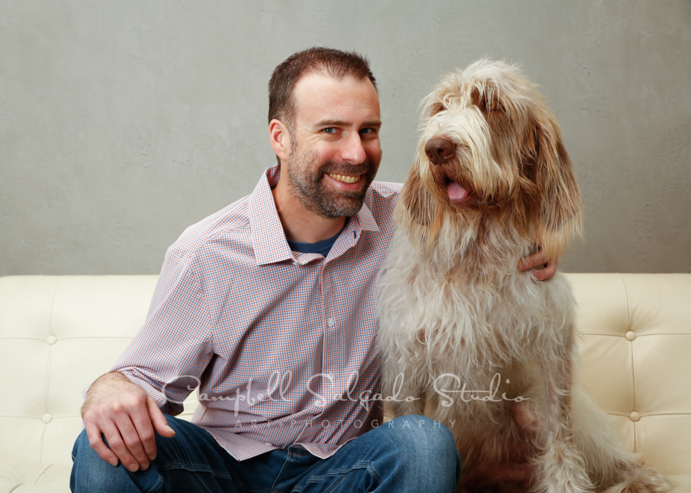 Portrait of man and dog on modern grey background by pet photographers at Campbell Salgado Studio in Portland, Oregon.
