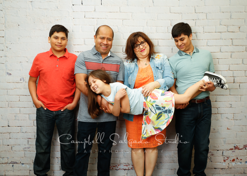 Portrait of family on ivory brick background by family photographers at Campbell Salgado Studio in Portland, Oregon.