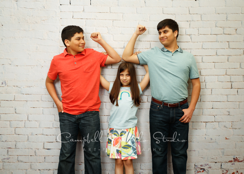 Portrait of kids on ivory brick background by children's photographers at Campbell Salgado Studio in Portland, Oregon.