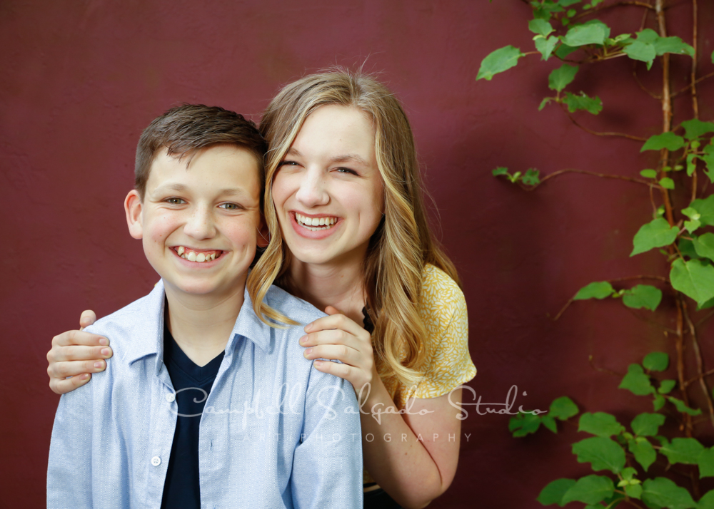 Portrait of children on plum stucco background by children's photographers at Campbell Salgado Studio in Portland, Oregon.