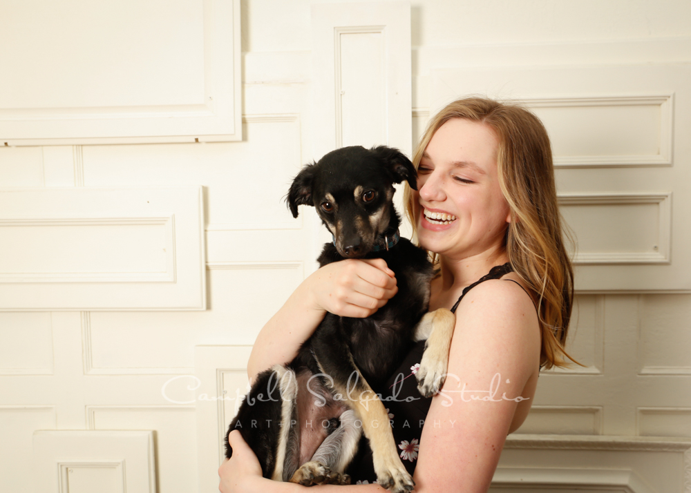 Portrait of teen and dog on antique ivory doors background by pet photographers at Campbell Salgado Studio in Portland, Oregon.