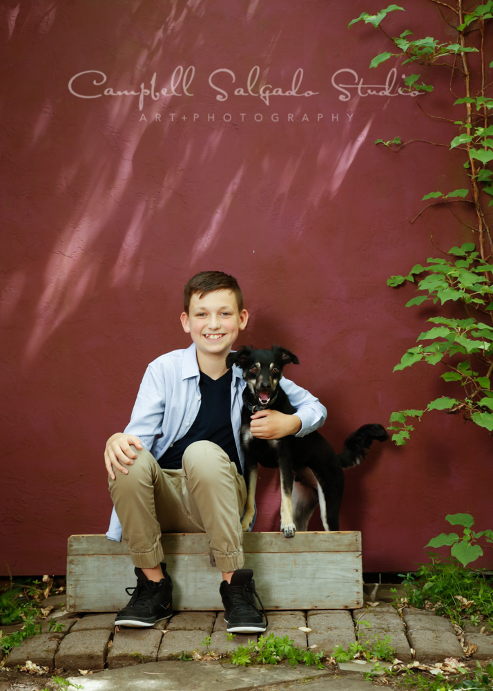 Portrait of boy and dog on plum stucco background by pet photographers at Campbell Salgado Studio in Portland, Oregon.