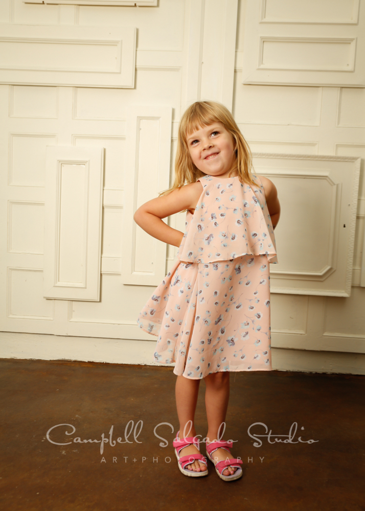 Portrait of girl on antique ivory doors background by child photographers at Campbell Salgado Studio in Portland, Oregon.