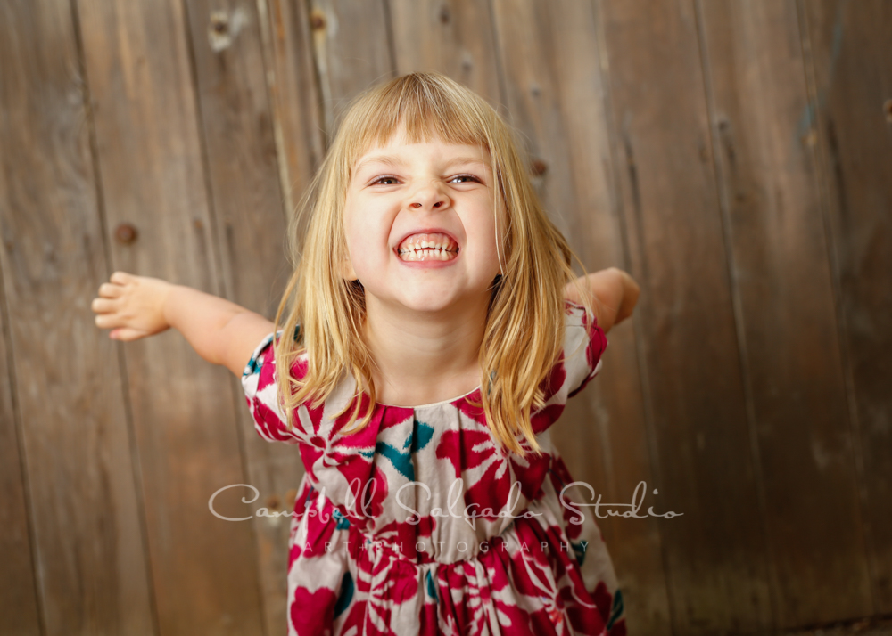 Portrait of girl on barn doors background by child photographers at Campbell Salgado Studio in Portland, Oregon.