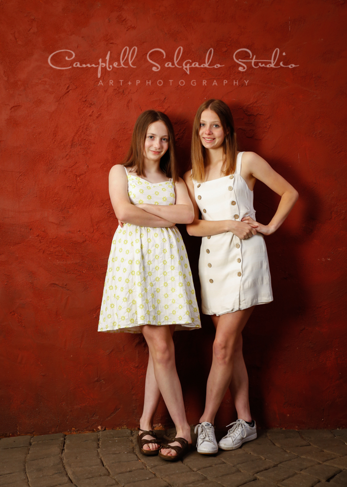 Portrait of girls on red stucco background by family photographers at Campbell Salgado Studio in Portland, Oregon.