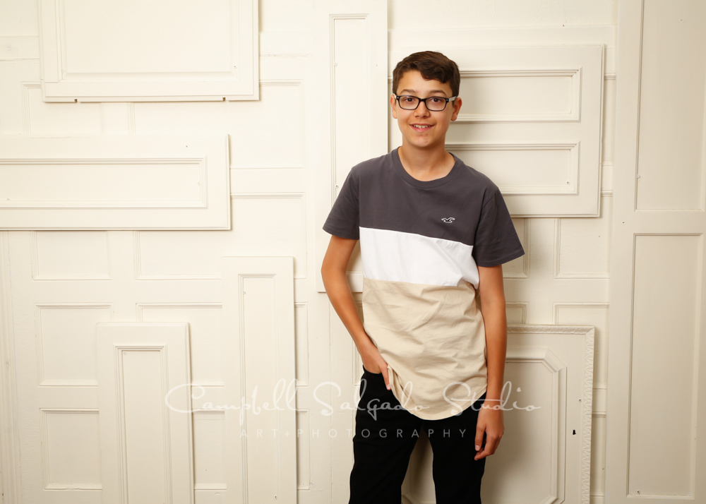 Portrait of teen on antique ivory doors background by teen photographers at Campbell Salgado Studio in Portland, Oregon.