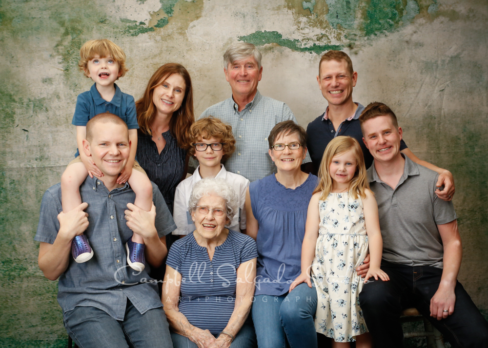 Portrait of multi- generational family on weathered green background by family photographers at Campbell Salgado Studio in Portland, Oregon.