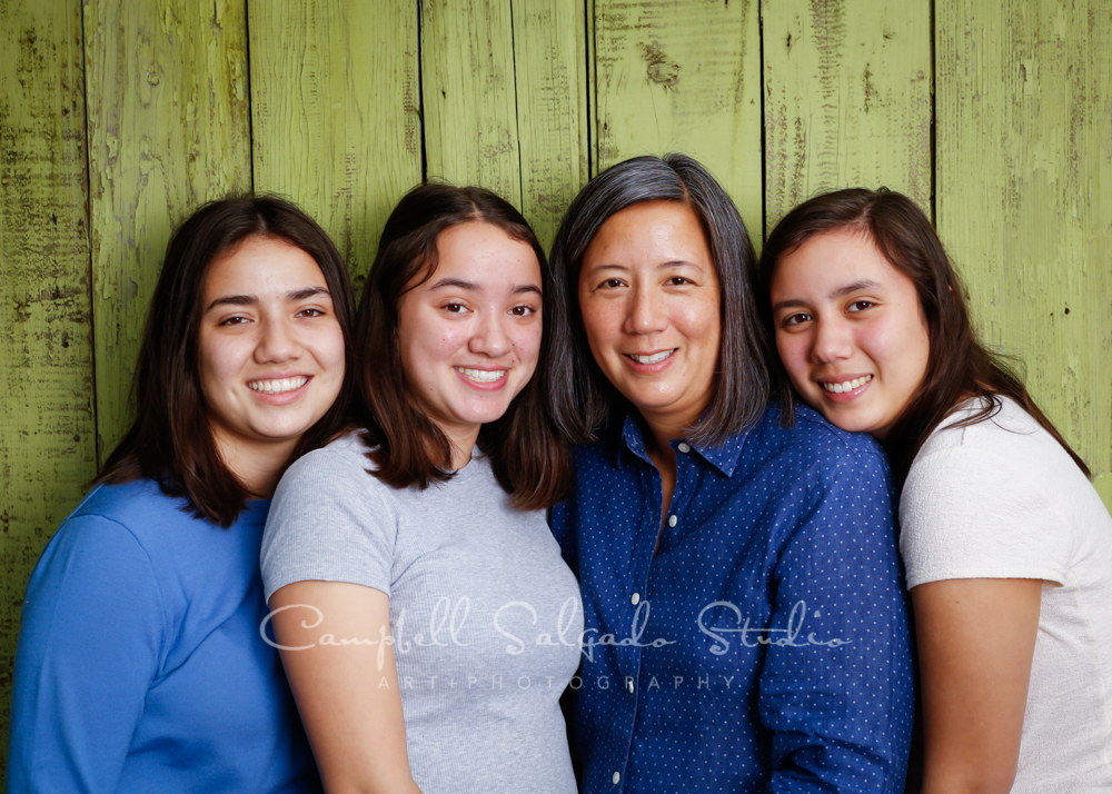 Portrait of mother and daughters on lime fenceboards background by family photographers at Campbell Salgado Studio in Portland, Oregon.
