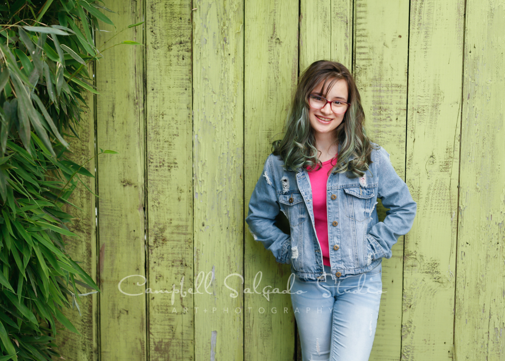Portrait of teen on lime fenceboards background by teen photographers at Campbell Salgado Studio in Portland, Oregon.