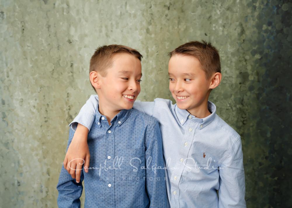 Portrait of twins on rain dance background by child photographers at Campbell Salgado Studio in Portland, Oregon.