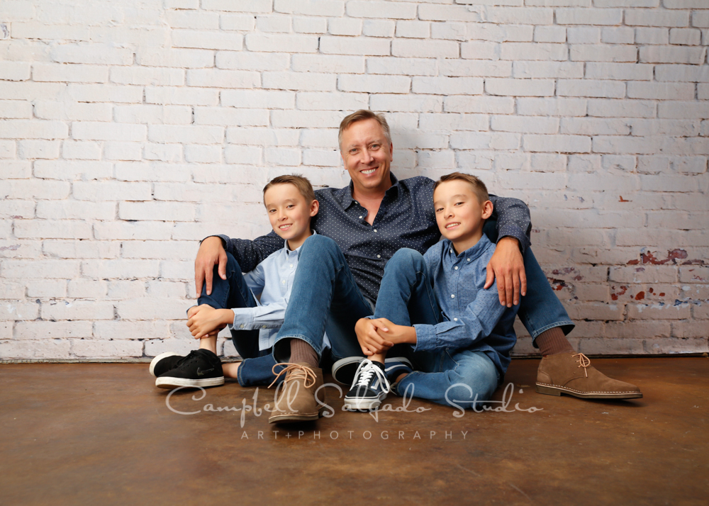 Portrait of family on ivory bricks background by family photographers at Campbell Salgado Studio in Portland, Oregon.