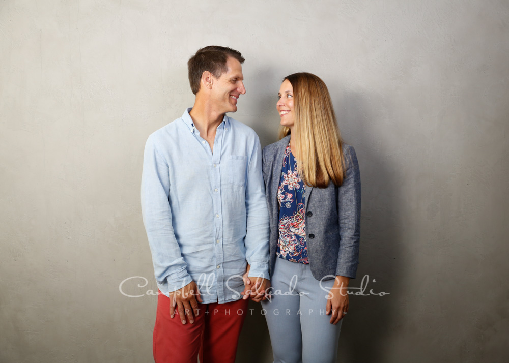 Portrait of couple on modern grey background by couple's photographers at Campbell Salgado Studio in Portland, Oregon.
