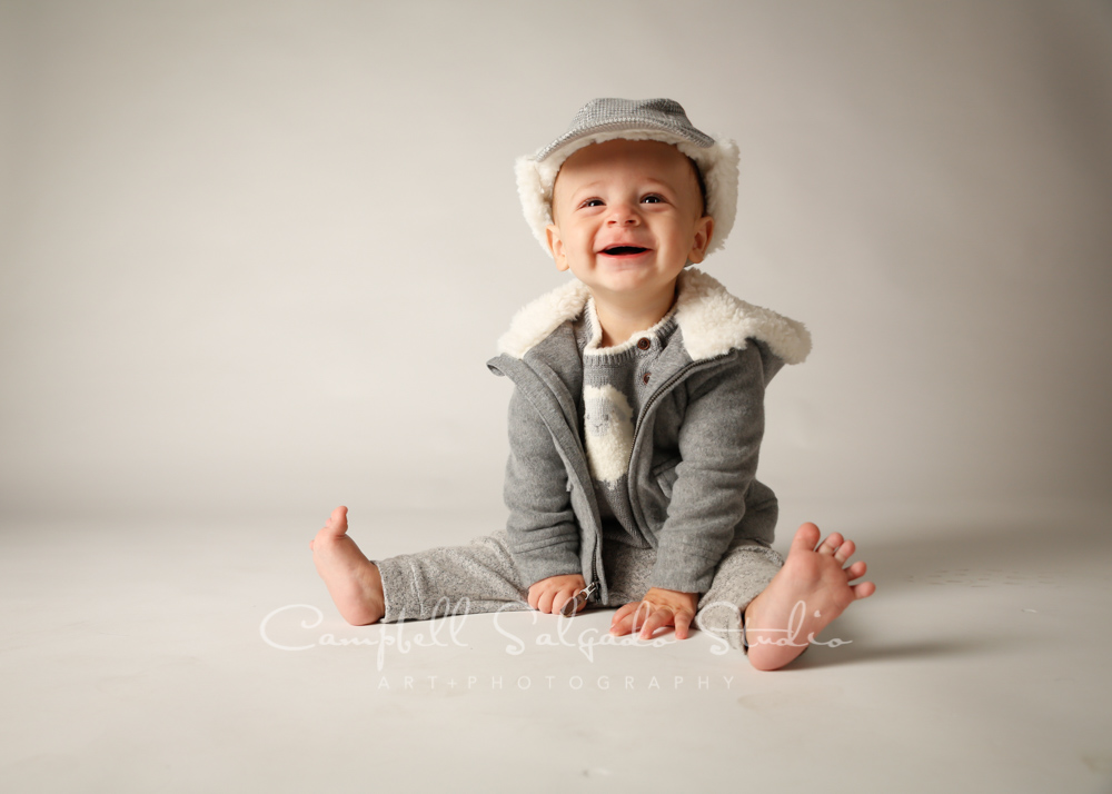 Portrait of baby on light grey background by child photographers at Campbell Salgado Studio in Portland, Oregon.