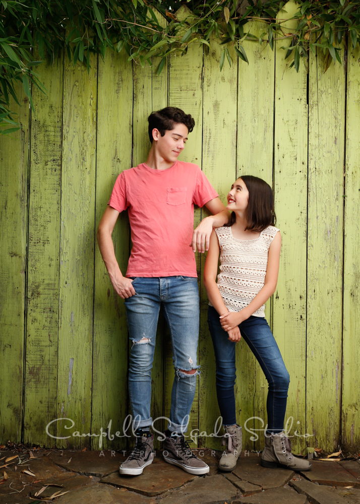 Portrait of siblings on lime fenceboards background by teen photographers at Campbell Salgado Studio in Portland, Oregon.