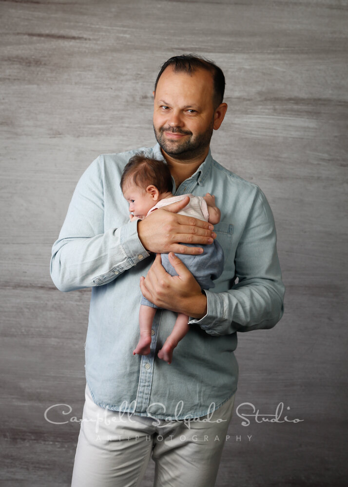 Portrait of father and newborn on graphite background by newborn photographers at Campbell Salgado Studio in Portland, Oregon.