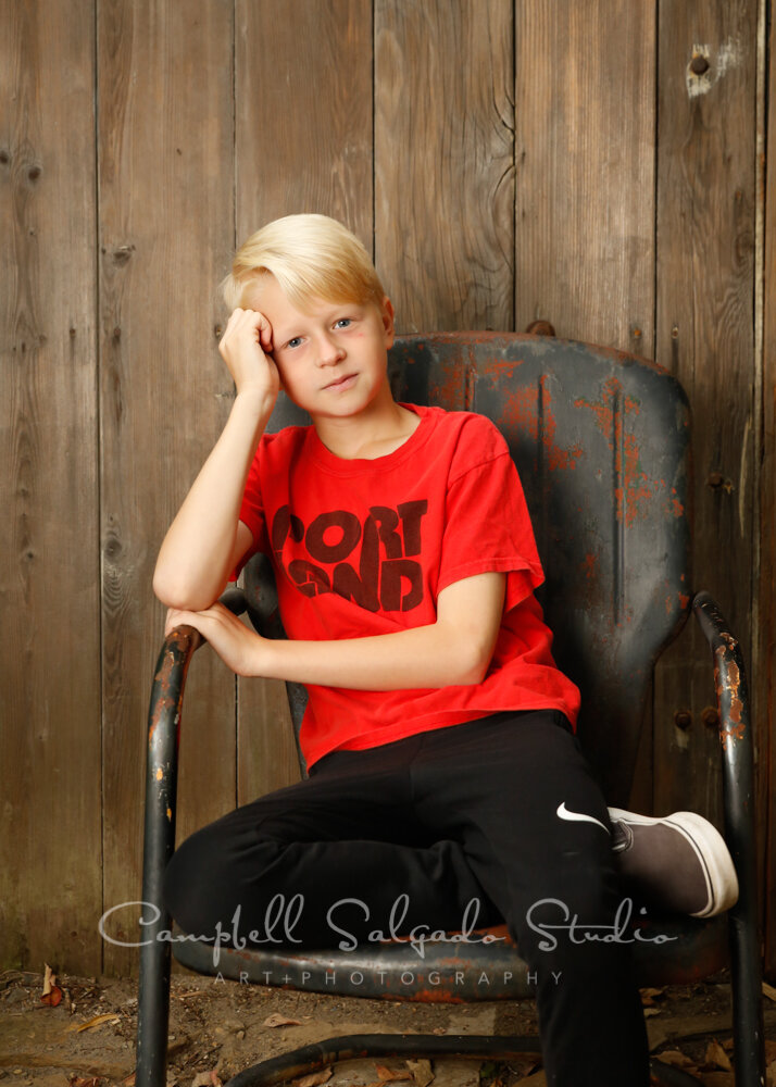 Portrait of boy on barn doors background by children's photographers at Campbell Salgado Studio in Portland, Oregon.