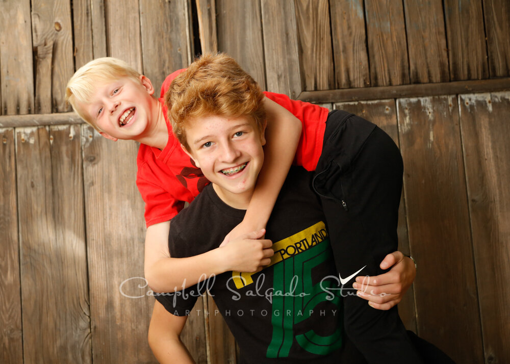 Portrait of boys on barn doors background by children's photographers at Campbell Salgado Studio in Portland, Oregon.