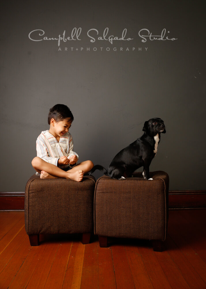 Portrait of boy and dog on grey background by pet photographers at Campbell Salgado Studio in Portland, Oregon.