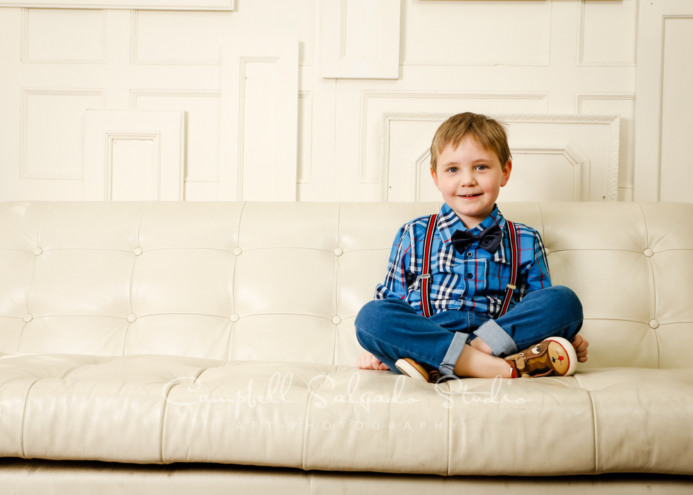 Portrait of boy on antique ivory doors background by child photographers at Campbell Salgado Studio in Portland, Oregon.