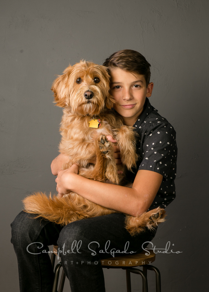 Portrait of teen and dog on grey background by teen photographers at Campbell Salgado Studio in Portland, Oregon.
