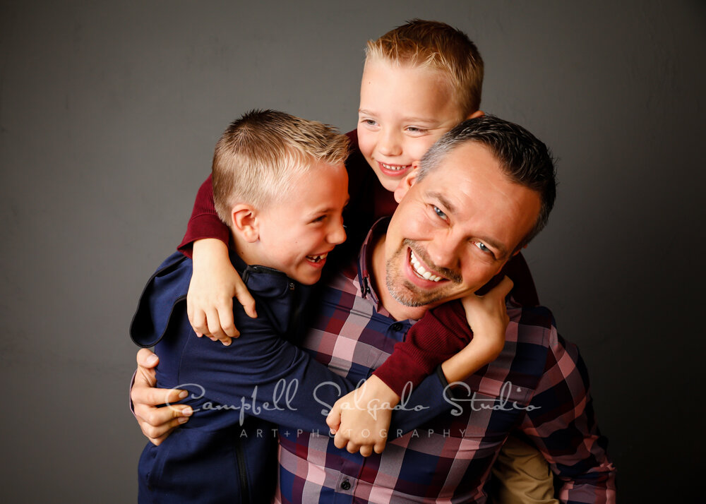 Portrait of boys and dad on grey background by child photographers at Campbell Salgado Studio in Portland, Oregon.