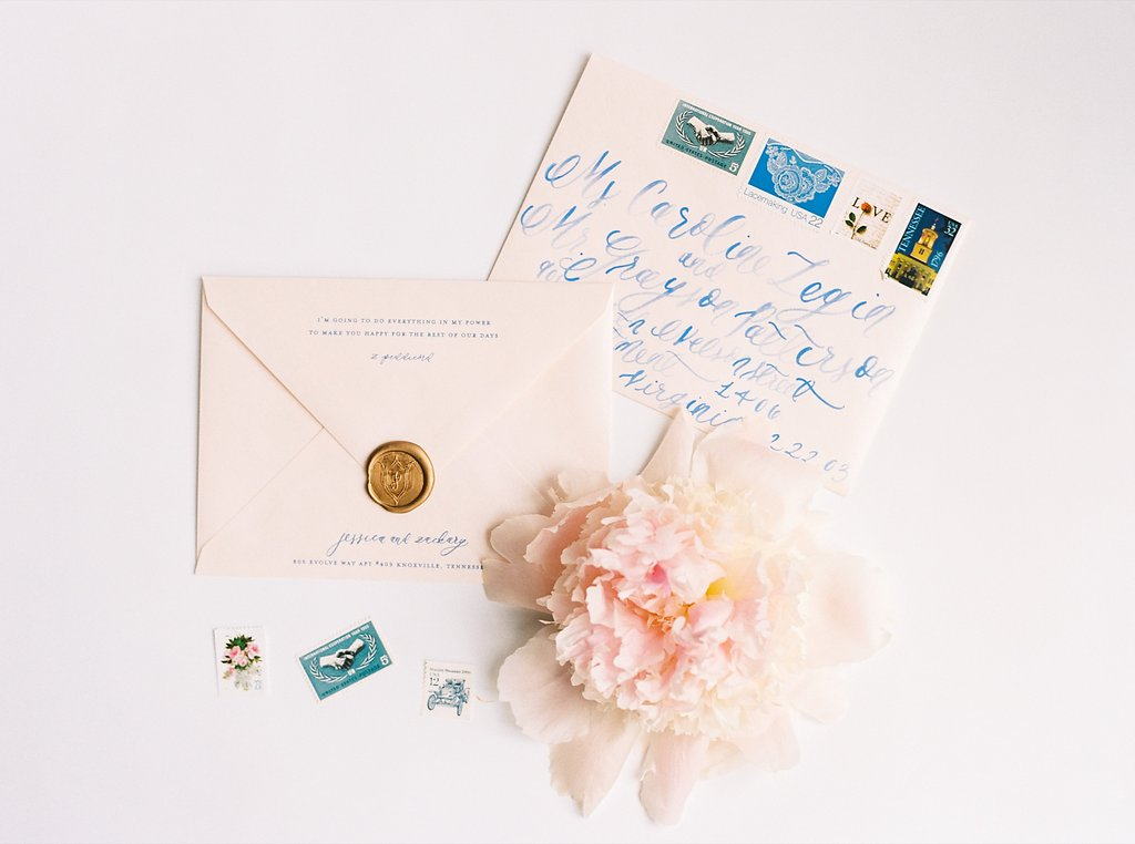 French Blue Brush Calligraphy on Metallic Blush Wedding Invitation Envelopes with Vintage Postage Stamps, Gold Wax Seals Featuring a Custom Wedding Crest, and a Sweet Love Note from the Groom Printed on the Back Flap Designed by Simply Jessica Marie | Blush and Navy Wedding with Fuchsia, French Blue and Gold Accents | Simply Jessica Marie's Southern Wedding at Gettysvue Golf Course and Country Club in Knoxville Tennessee | Photo by Perry Vaile Photography