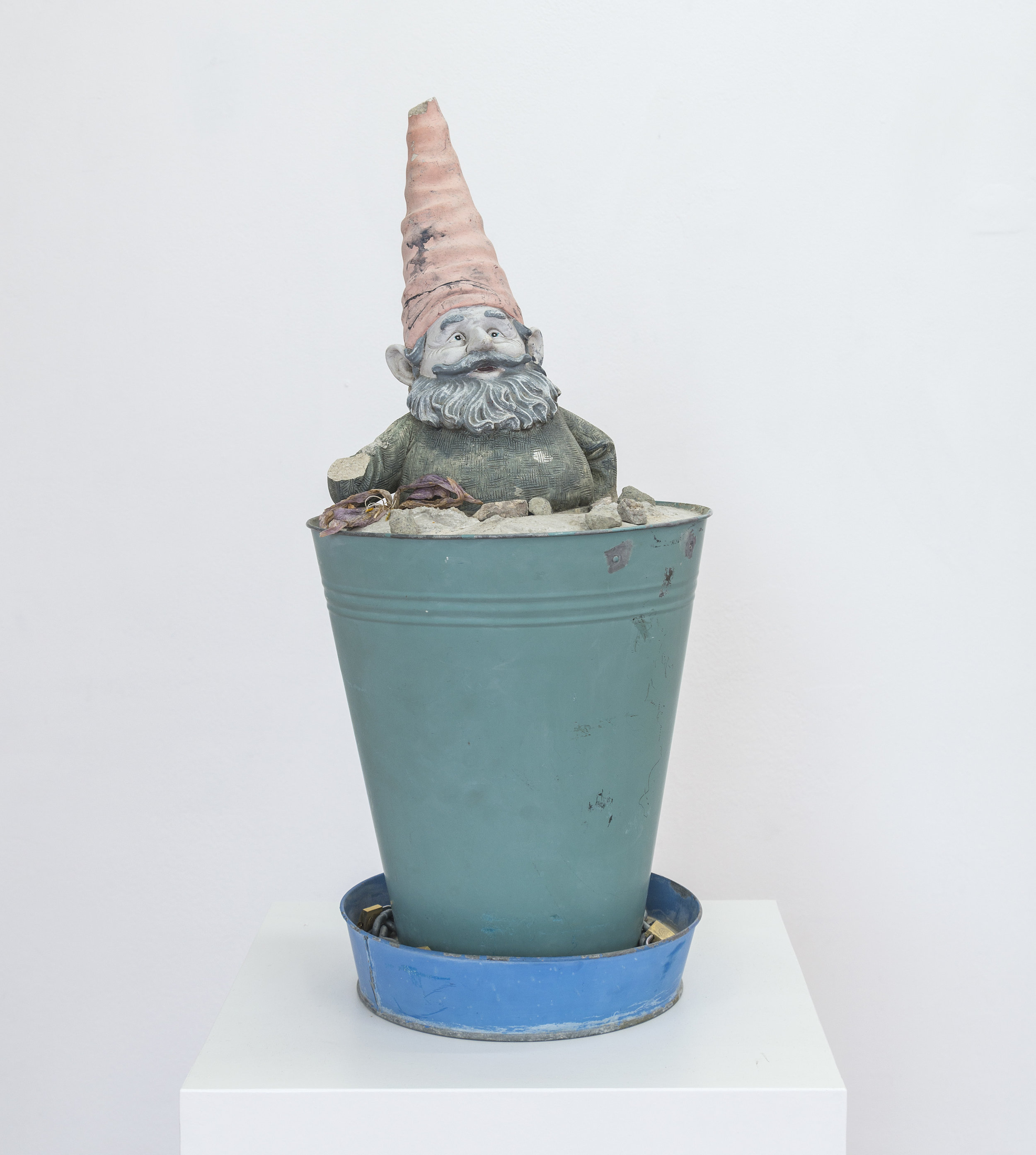 Stab in the dark, 2019   Gnome, metal plant pot, concrete, dead flower, chain and lock, rocks on white pedestal 11x25x10 inches