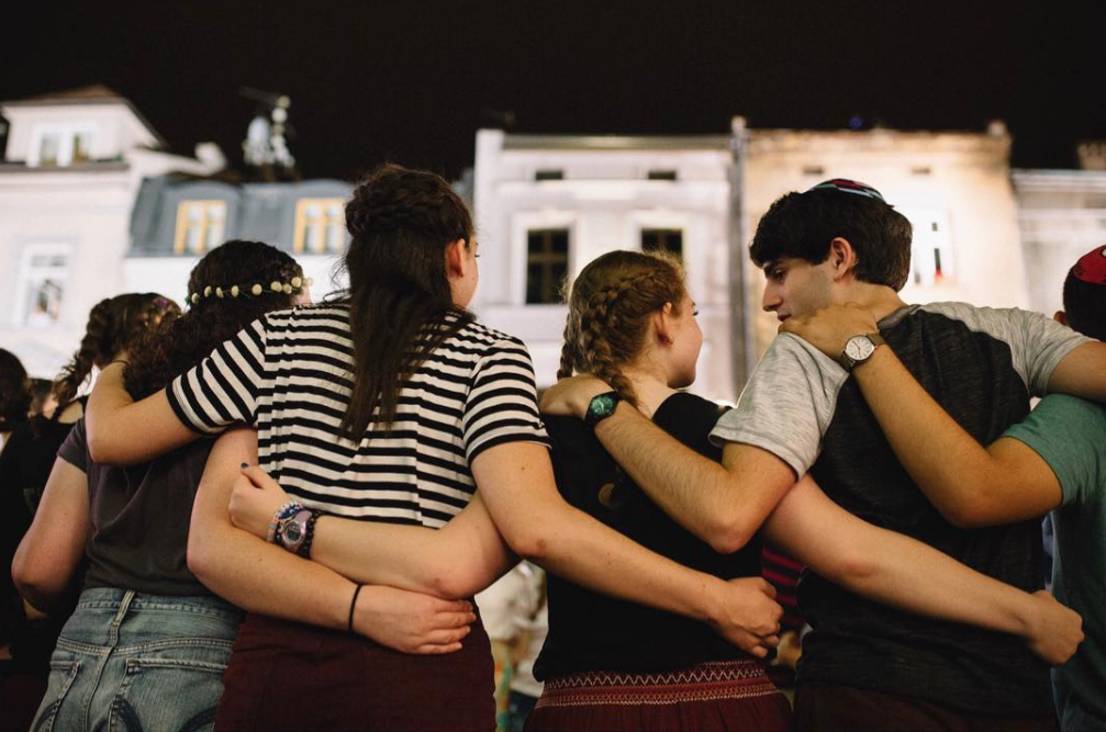 Overcome the Passive VIII: the Jewish Culture Festival, Kraków. A group of visiting teenagers embrace on the open streets of Kraków; international youth make the annual pilgrimage as part of local faith and culture programs, mainly based in the USA, to attain a deeper meaning of their history and what it is to be a Jew.